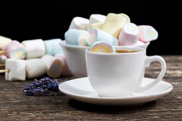 Сладкий мягкий зефир из натуральных ингредиентов и натуральных цветов, сахарный десерт крупным планом, чашка кофе