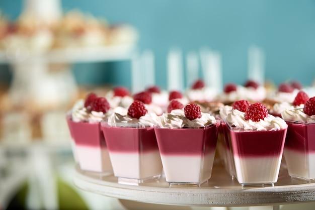 ラズベリーとホイップクリームで飾られた甘いスフレ。レストランのケータリングやキャンディーバーのおいしいデザート。