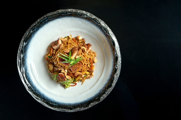 Sweet and sour noodles with pork, peanuts, vegetables and onions, served in a white bowl. wok noodles.