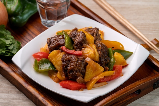 Sweet and sour sauced deep fried pork ribs with chopped pepper and pineapple in a plate on wooden table