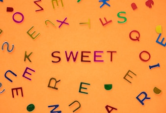 Sweet spelled word with alphabets background