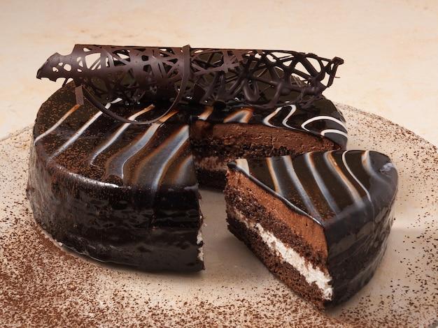 Сладкий бисквитный шоколадный торт на тарелке, украшенной какао-порошком