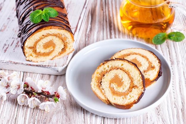 Сладкий бисквитный рулет с начинкой из сливок. сладкая еда пустыни