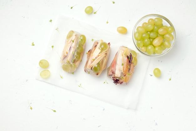Сладкие блинчики с начинкой из фруктов рядом с свежим виноградом на белом. сладкое без сахара