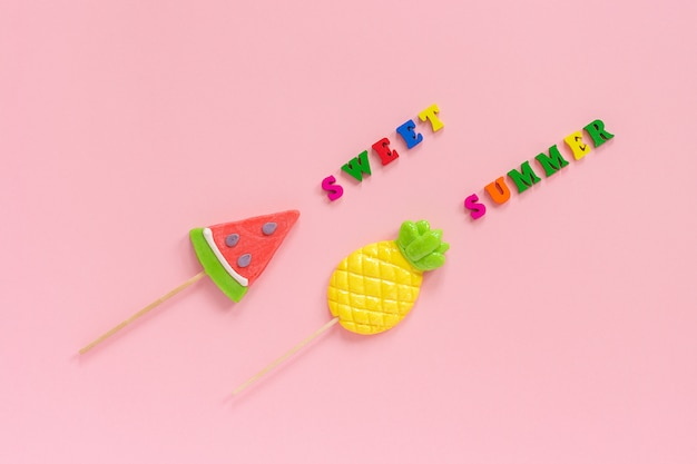 Sweet summer text, pineapple and watermelon lollipops on pink background.