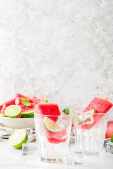 白い大理石の表面に甘い夏のスイカとライムのアイスキャンデースライスしたスイカとミント、