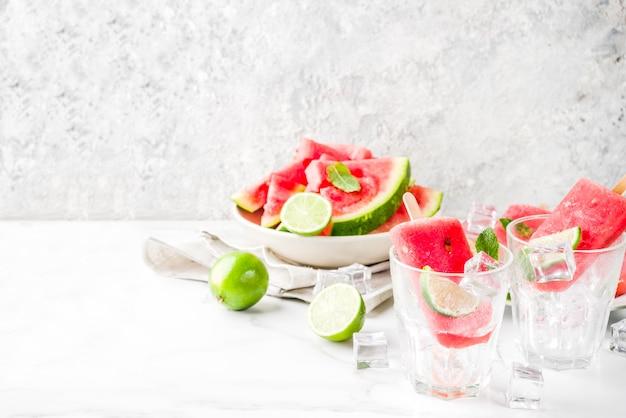 白い大理石のテーブルの上にスライスしたスイカとミントの甘い夏スイカとライムアイスキャンディー
