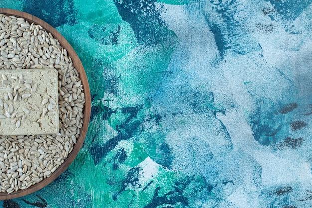 Сладкая халва подсолнечника с семенами на деревянной тарелке, на синем столе.