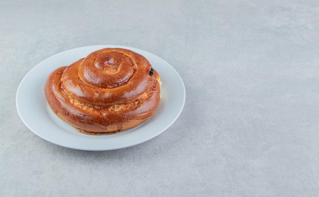 Panino dolce di turbinio sul piatto bianco.