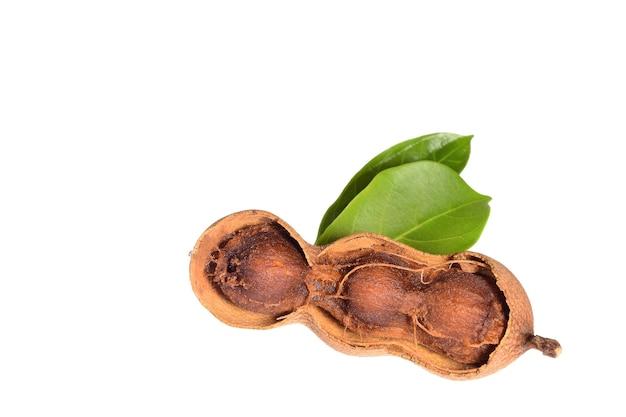 甘いタマリンドの果実と白い背景で隔離の葉。