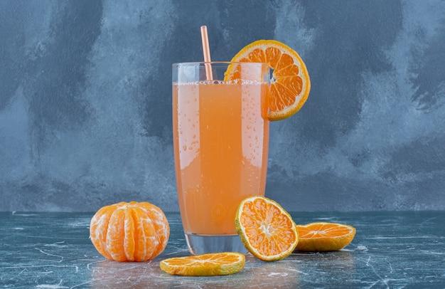 Mandarino dolce e succo sul tavolo blu.