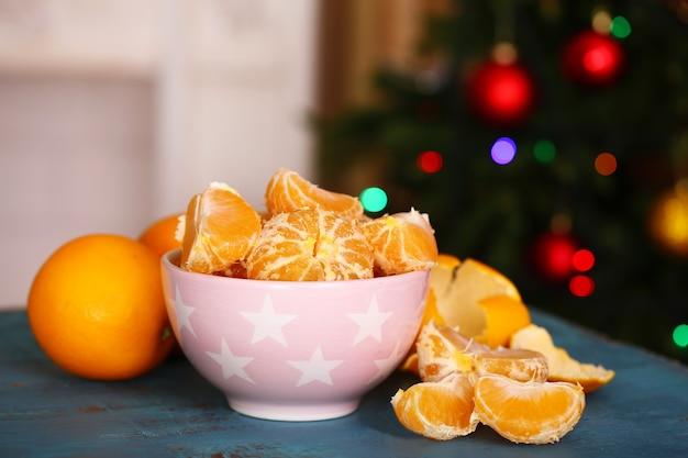 Сладкие мандарины и апельсины на столе с елкой позади