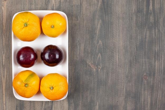 Сладкие мандарины со сливами на деревянном столе. фото высокого качества