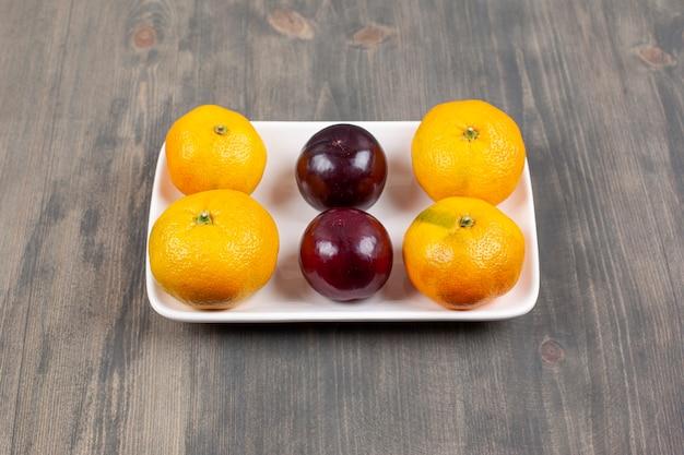 나무 테이블에 자 두와 달콤한 감귤. 고품질 사진