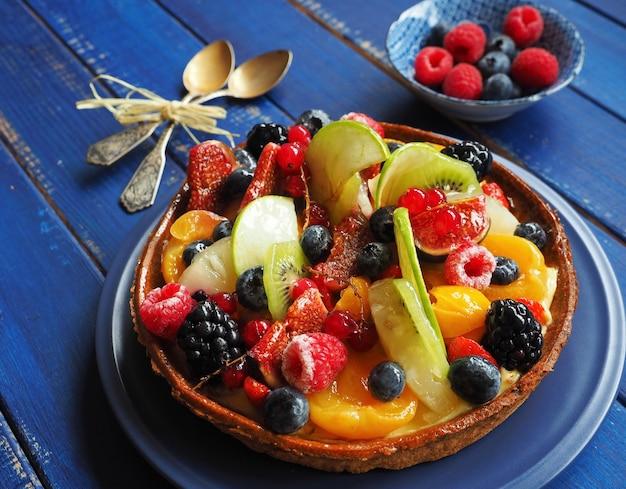 青い木の表面にエキゾチックなフルーツとベリーの甘いタルト