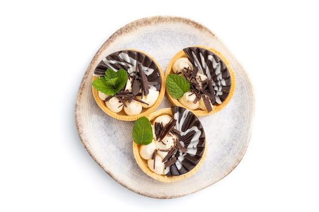 Сладкие тарталетки с шоколадом и сырным кремом, изолированные на белом фоне. вид сверху, плоская планировка, крупный план.