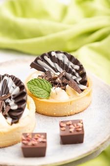 Сладкие тарталетки с шоколадом и сырным кремом с чашкой кофе на сером фоне бетона и зеленой ткани. вид сбоку, крупным планом, выборочный фокус.