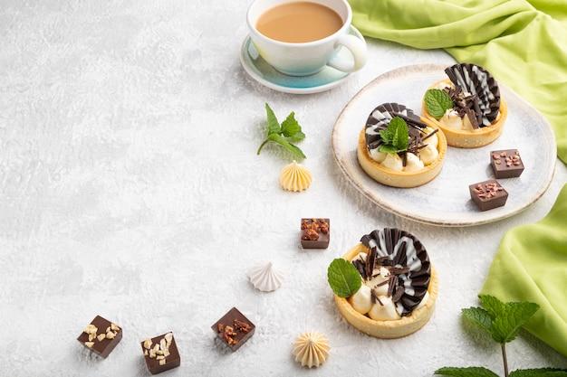 灰色のコンクリートの背景と緑のテキスタイルにコーヒーカップとチョコレートとチーズクリームの甘いタルト。側面図、フラットレイ、コピースペース。
