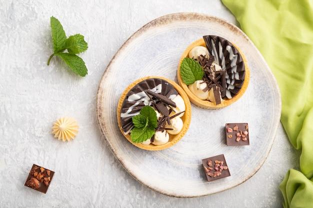 灰色のコンクリートの背景と緑のテキスタイルにコーヒーカップとチョコレートとチーズクリームの甘いタルト。上面図、フラットレイ、クローズアップ。