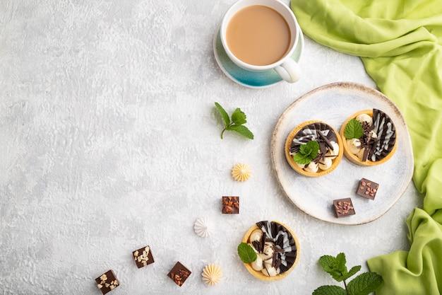 灰色のコンクリートの背景と緑のテキスタイルにコーヒーカップとチョコレートとチーズクリームの甘いタルト。上面図、フラットレイ、コピースペース。
