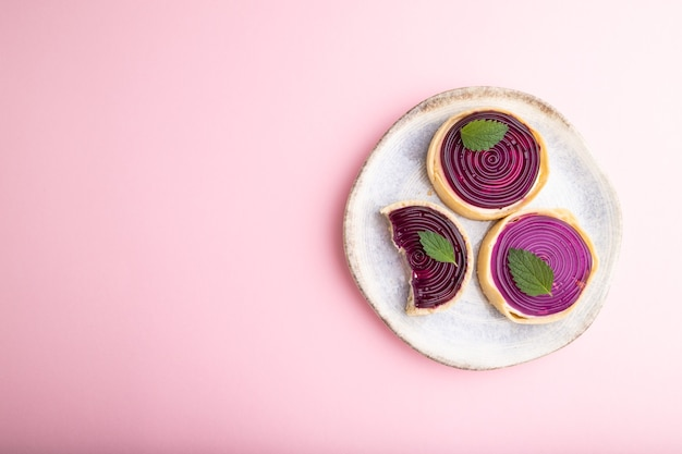파스텔 핑크 배경에 젤리와 우유 크림과 함께 달콤한 tartlets. 평면도, 평면 위치, 복사 공간.