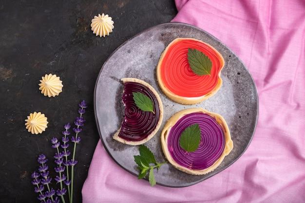 검은 콘크리트 배경과 분홍색 섬유에 커피 한잔과 함께 젤리와 우유 크림과 함께 달콤한 tartlets. 평면도, 평면 누워, 닫습니다.