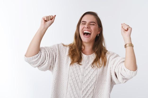 甘い味の勝利。肖像画非常に幸せな魅力的な若い女性のジャンプ幸せを祝う勝利を上げる握りこぶし成功達成ジェスチャー、夢の実現、目標を達成する