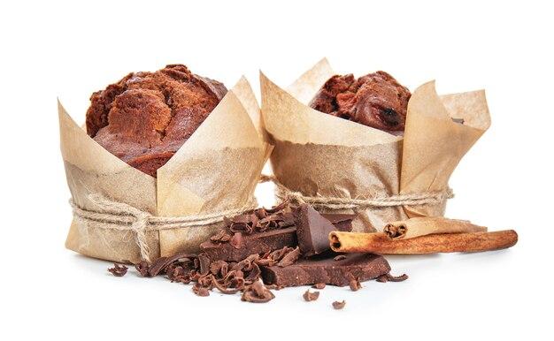 白い背景にシナモンスティックとチョコレートと甘いおいしいマフィン