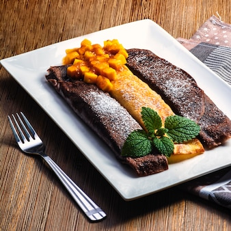Sweet tasty pancake, homemade pancake with chocolate. healthy and tasty food with blackberry, mango fruits and mint.