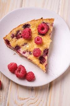Сладкий вкусный кусочек пирога с заливными и свежими плодами малины в тарелке, деревянный стол, угловой вид