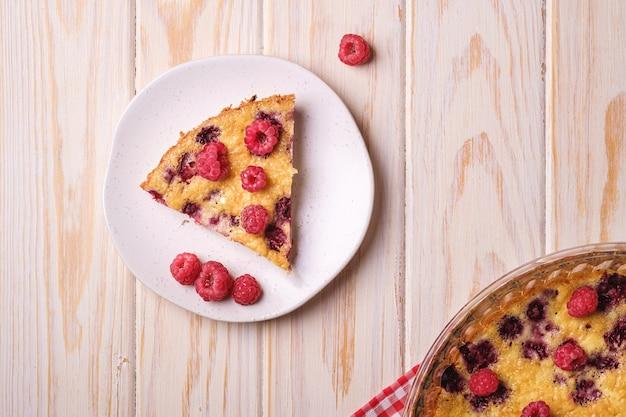 Сладкий вкусный пирог с заливными и свежими плодами малины в форме для выпечки и тарелке с красным скатертью, полотенцем, деревянным столом, видом сверху