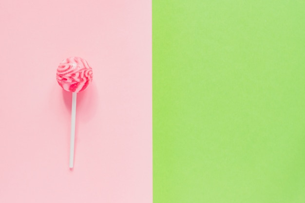 Sweet tasty pink lollipop on green and pink background. minimal flat lay with copy space