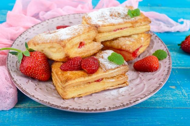 Сладкий вкусный десерт из слоеного теста на табличке на деревянных фоне. вкусное домашнее печенье с клубничным джемом, ягодами и сахарной пудрой.