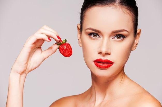 甘い誘惑。灰色の背景に立っている間彼女の手でイチゴを保持している美しい若い上半身裸の女性
