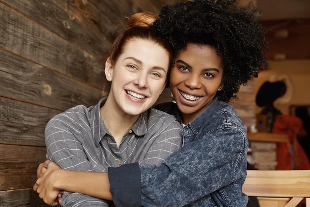 幸せな異人種間の同性愛者カップルがカフェで抱きしめると抱きしめるの甘い柔らかい屋内ショット