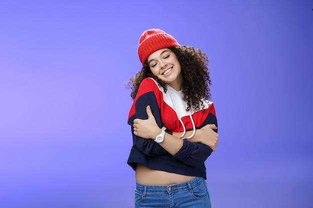 Dolce tenera e sensuale donna dai capelli ricci in berretto rosso alla moda che si abbraccia con gli occhi chiusi e un sorriso nostalgico appoggiato sulla spalla sentendo calore e tenerezza come ricordando ricordi d'amore.