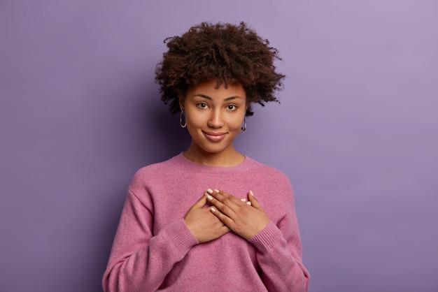 Dolce grazie. affascinante donna afroamericana sincera e toccata apprezza la sorpresa o il regalo adorabile, tiene i palmi premuti sul cuore, essendoti molto grato, posa contro il muro viola