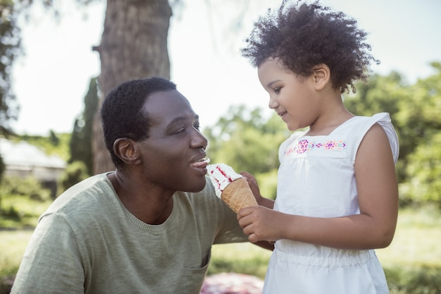 Sweet time. curly-haired cute kid eating ice-cream and spending time with dad