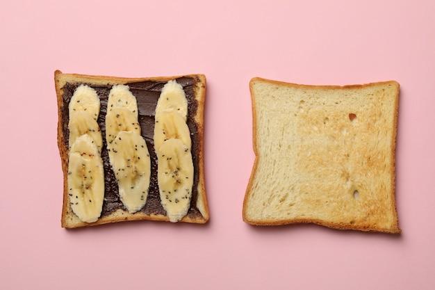 Sweet toast with banana on pink background Premium Photo