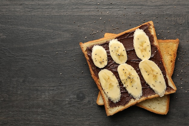Sweet toast with banana on wooden background