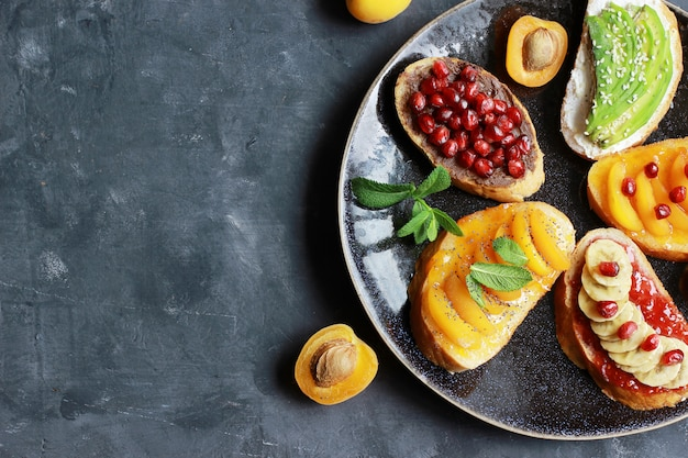 잼과 다양 한 과일 살구, 바나나, 석류와 어두운 배경 복사 공간 평면도에 아보카도 달콤한 토스트.