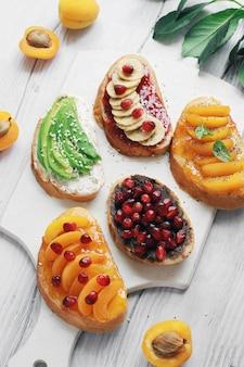 잼과 다양한 과일 살구, 바나나, 석류 및 아보카도와 달콤한 토스트.