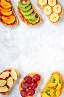 Sweet toasts for breakfast with peanut butter, strawberry jam, banana, grapes, peach, kiwi, pineapple, nuts. copy space