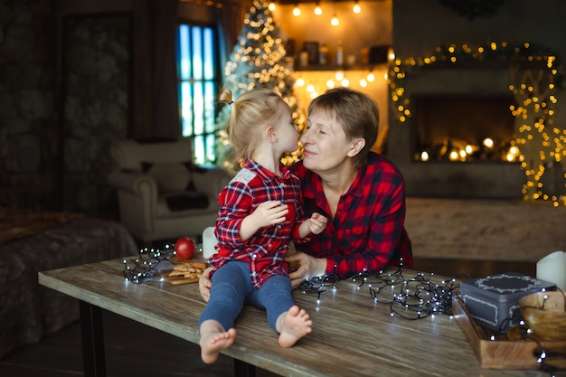 A sweet toddler kisses her grandmother in the nose, sitting on a wooden table in a hunting house decorated for christmas.
