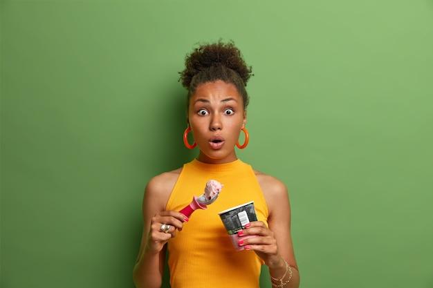 Concetto di golosità e tentazione. donna afroamericana sorpresa senza parole mangia un gustoso dessert freddo, si gode un gelato al gusto di fragola, vestita con abiti estivi gialli, parete verde