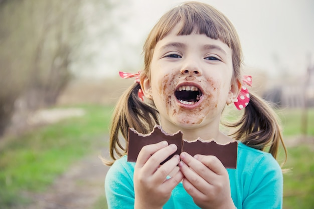 A sweet-toothed child eats chocolate. selective focus.