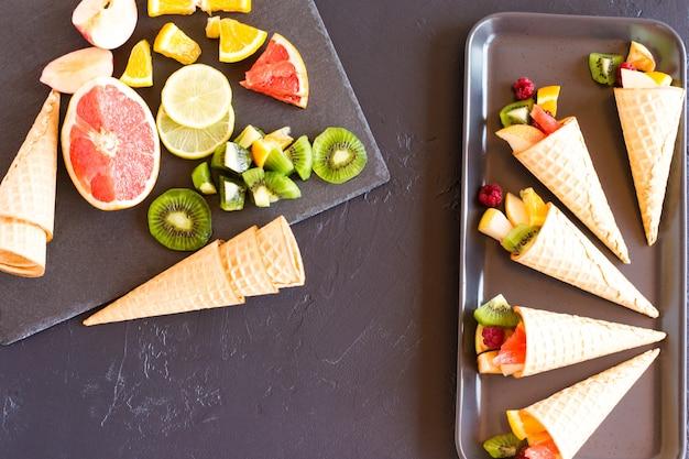 휴가를 위한 달콤한 대접. 잘 익은 과일과 와플 콘입니다. 평면도.