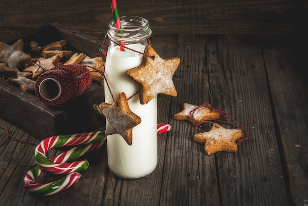Sweet and treats, bottles with milk for santa with gingerbread star cookies with  decoration rope, old wooden ,
