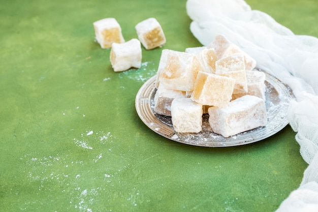 Sweet turkish delight on plate on green table