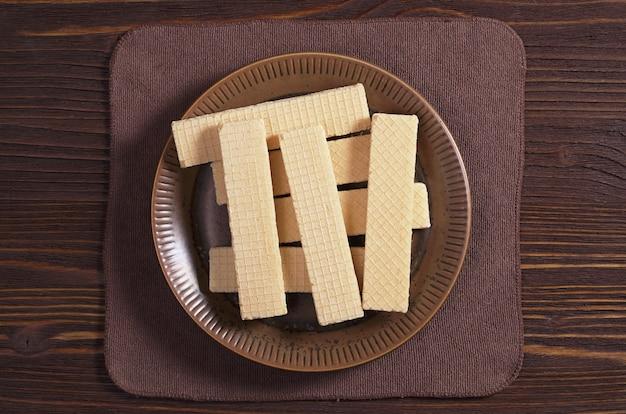 Сладкие вафли в тарелке на коричневом деревянном столе